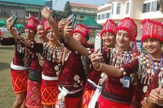 Girls draped in traditional Singpho costumes taking selfie during Dibrugarh University Inter College youth festival