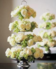 Arranjo de mesa com rosas e uvas verdes.