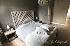 A beautiful beige headboard with white bedding and grey walls.