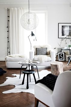 love this space. tall bendy lamp that doesn't swing way out, wood floors, white walls and curtains, white hide rug, big graphic number, so much texture, good balance of contrasting black