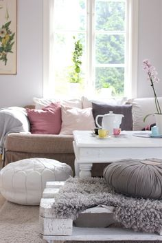 Pallet with gray throw and floor pillow. White pouf and white coffee table with comfy styling. <3