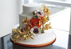 White Wedding Cake with Swiss dots, sugar flowers- ranunculus, anemone, clown orchids -Handmade by Finespun Cakes & Pastries