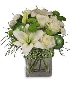 White roses and lilies with lime green button poms and glitter ornaments in a lovely square vase decorated with festive beads.