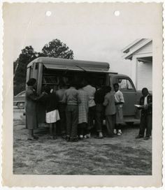 This image shows patrons using the bookmobile service from the Orangeburg County Library. Back of the image reads 'Negro Service, Orangeburg County Library, 1950.' http://digital.tcl.sc.edu/cdm/ref/collection/scslchldrn/id/13