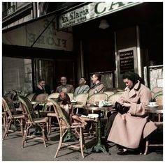 Alla and her dog sitting at Cafe de Flore,Paris, 1952. Photo by Robert Capa.