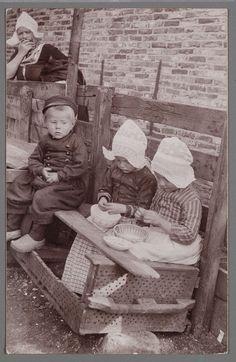Garnalen pellen. 1905-1910. Garnalenpelsters van de Fa. Jansen. Een viskaar is verbouwd tot bank. Twee meisjes in dracht met hul zijn aan het pellen. Een jongen en op de achtergrond een vrouw kijken toe. Volendam