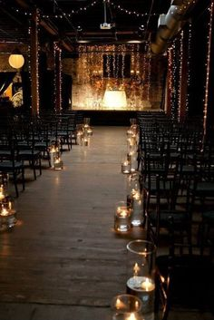 Floating tea candles and strings lights soften the industrial feel of this walk down the aisle.