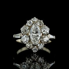 Antique Platinum and 14K White gold diamond cluster ring featuring a .95 carat marquise cut diamond (H color, I1 clarity) wreathed with a border of antique old mine cut diamonds and set with a tapered baguette cut diamond on each shoulder. Side diamonds weight a total of 1.75 carats (H-J color, SI1-I1 clarity).