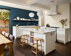 photo of bespoke colourful contemporary modern teal white walnut harvey jones kitchen with lighting shelves hardwood floor island and stools