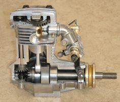 The HP VT21 (21cc) was the smallest of the VT series which included a 49 and 61- all with a shaft-driven rotary sleeve valve. Note the vertical shaft behind the cylinder extends upward to a pair of spur gears. The large gear is connected to a vertical drum type valve that rotates through the intake, combustion, and exhaust cycle as the engine runs. As seen here the hole in the drum is half way between the exhaust and intake ports. As the crankshaft turns counter-clockwise the hole in the…