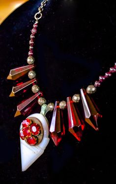 Lovely white glass talhakimt hung with an antique red rhinestone pin. Strung with pyrite beads, garnet rounds, and red chandelier crystals. Loose