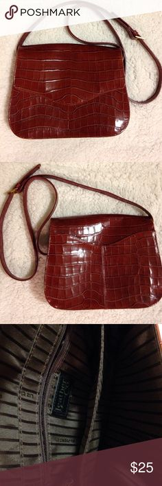 Liz Claiborne cross body purse Brown leather is embossed in an alligator pattern. The back of purse has storage compartment. The interior of purse has 4 storage compartments and one compartment had a zipper closure. Purse measures 20 inches across, 6 inches high and 2 3/4 inches wide. The strap has 23 inch drop and can be made longer or shorter. Hardware on purse is gold tone in color Liz Claiborne Bags Crossbody Bags