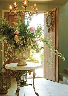 I love this foyer...the beautiful wood doors, the warm green walls , serve as a great back drop for the table and oversized flower arrangement...fabulous !!!