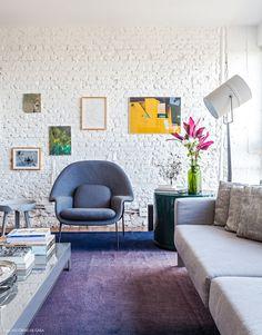 Poltrona Womb de Eero Saarinen e mesinha lateral da marca Muuto completam a decoração do apê.