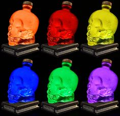 Upcycled Crystal Skull Vodka Bottle Lamp by DiamondLiquorLights. The image displays 6 colours out of a posible 16. The wooden base has been cut with a slot and cove profile, then hand painted in textured black and silver paint.