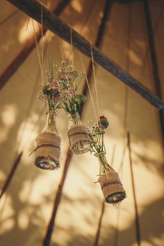 Hanging Milk Bottle Decor wrapped in hessian & filled with Wild Flower Stems   Lace Augusta Jones Dress   Summer Country Wedding   Outdoor Tipi Reception   Rustic Decor   Wild Flowers   Etsy Purple Bridesmaid Dresses   Festoon Lights   Helen Lisk Photography   http://www.rockmywedding.co.uk/eve-tim/