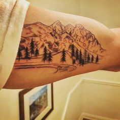 My second tattoo. The mountain range is made up of 3 peaks I've skies or hiked. Breckenridge (left) Grand Tetons (middle) Angel's Landing Zion (right). Mountain tattoo. Pine tree tattoo. Mountain range tattoo. Outdoorsy. rustic. stream. Bicep tattoo.