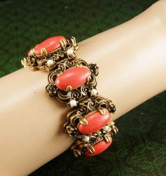 "WOW ! WHAT a fantastic old bracelet ! It is really heavy and wide ( 1 1/4"") and made with elaborate thick metal work that encompass these gorgeous faux salmon color coral cabochons. This is such a well..."