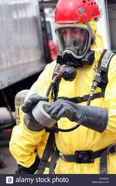 A firefighter using duct tape to secure the hazmat suit at a chemical haz mat spill incident Stock Photo