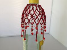 Red with clear accent glass beads wine bottle cover; by Radiance Collectibles.