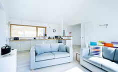 white kitchen and bright living room in a timber clad self build