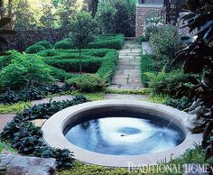 A spa pool tucked away in a densely planted area is an alluring feature of this garden. - Traditional Home ® / Photo: Matthew Benson / Design: Mary Zahl
