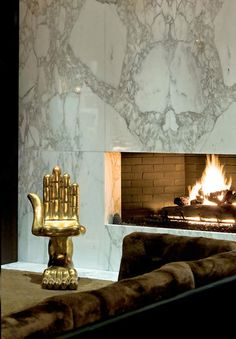 OMG THIS CHAIR!  Pedro Friedeberg Hand Chair next to a White Fireplace #marble #midcenturydesign