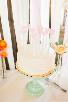 Beautiful white single tier wedding cake with heart cake toppers