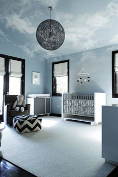 A unique modern blue, white, and black nursery with a wonderful cloud mural on the ceiling and walls.