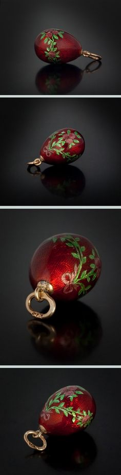 A Faberge Gold Mounted Guilloche Enamel Egg, made in St Petersburg between 1908 and 1917, The miniature egg pendant is covered with a strawberry red guilloche enamel and painted with ribbon tied rose garlands over underlying silver foil.