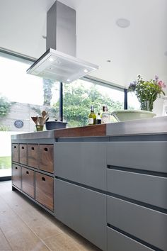 Contemporary kitchen with walnut wood storage drawers. Stainless steel worktop, grey cabinets, extractor hood. integrated appliances