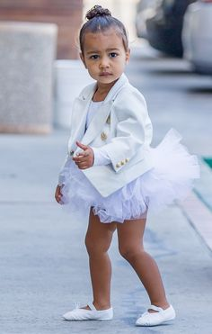 north-west-ballet-bun I'm late for class.Gotta run. Ok! One pic won't hurt. How cute white on white from head to toe. High center,curly bun/w baby hair softly framing her hair line, white tuxedo jacket with gold buttons, white tutu and white ballerina shoes to complete this over the top look for baby #NorthWest