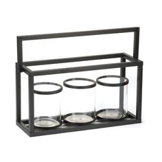 Glass Jar Candleholder Trio - A trio of clear glass candle cups are set in black metal to create a dramatic display of candlelight. Add the candles of your choice and light them to fill the room with modern glow.