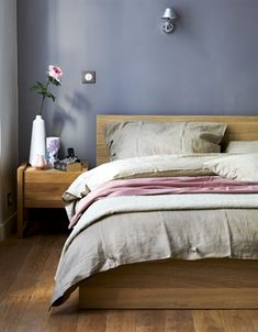 grey walls.     A bedroom with oak furniture and grey/pink textiles