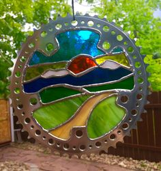 Stained glass within a recycled bicycle chain ring, mountain and trail during sunset. https://www.etsy.com/shop/NightShiftGlass