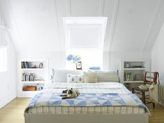 The built-in shelves that bookend the bed are actually doors that open to storage closets for bulky items like suitcases.