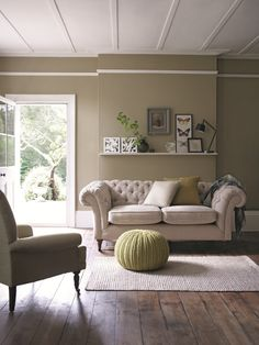 Decorate your living room with neutral sofas and inject green into the cushions and other decor.