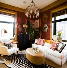 Red living room with white sofas and zebra rug