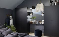 Dark bedroom furniture can make the room feel spacious, too. Try putting a wall of mirrors and a vanity table between two black-brown PAX wardrobes. The wardrobes from IKEA have black doors and lots of room inside to get organized.