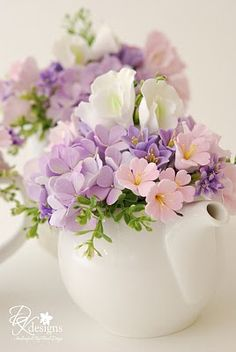 Teapot with cherry blossoms, lavender hydrangeas, lavender hyacinth, pink and white sweet peas. (DK designs)