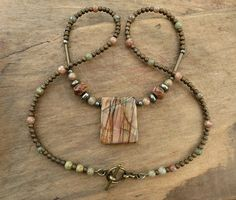 I created this earthy yet artistic Picasso jasper necklace using a stunning Picasso jasper pendant flanked iron pyrite and additional jasper beads. The pendant's muted earthy colors and intricate markings are reminiscent of an abstract painting with a naturally pleasing palette and composition.   The remainder is made up of Japanese seed beads and jasper spheres. It is finished with a brass toggle clasp.