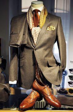 Men's taupe suit, ivory shirt, print neck & lapel scarf, w/ cognac color tie & wing tip shoes.