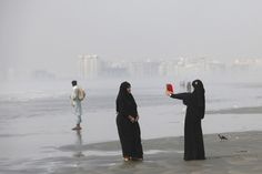 Girls clad in burkas take picture with a tablet while visiting Karachi's Clifton Beach