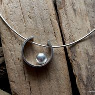 This pendant features a solid silver 'pebble' which rests inside a silver horseshoe. The horseshoe measures approx 24mm across and 6mm wide. A 1.2mm, 40cm omega chain is threaded through the horseshoe and fastens with a bolt ring. Shipped in an organ...