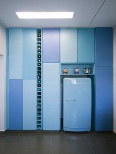 Cozinha colorida em tons de azul, com geladeira retrô, toy arts, armários embutidos e espaço para guardar garrafas, faz parte de apartamento com decoração moderna, retrô e jovem, criado pelo FCstudio