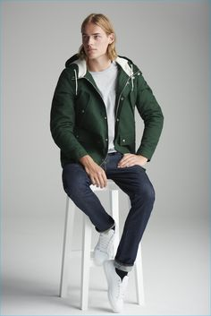 desportivo em uma jaqueta com capuz verde e calça jeans para o River Island outono-
