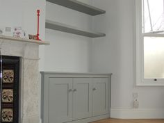 This three door cupboard was fitted into a larger than usual alcove. It is finished in a Farrow & Ball grey with floating shelves fitted above.