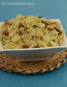 "Flaked rice and papad sautéed with spices, peanuts and coconut. Use a thin variety of poha commonly known as ""nylon poha"", to make a crispier snack. This recipe can be stored in an air-tight container for several days. Add the roasted and crushed papad to it just before you are ready to serve."