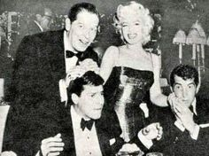 Jerry Lewis has Milton Berle bearing down on him while Dean Martin gets to kiss  Marilyn Monroe's hand.