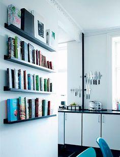 cocina en blanco y negro con toque de color y zona de libros